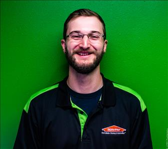 Male employee in front of green wall
